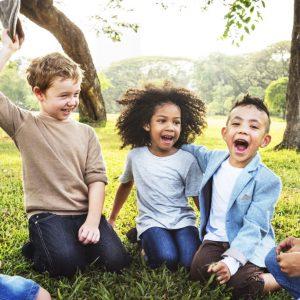 Kinder-sitzen-im-Gras-auf-der-Wiese