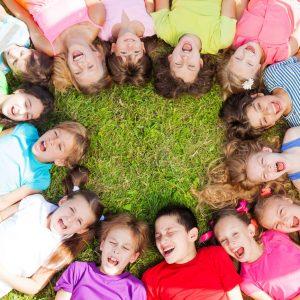 Kinder-liegen-im-Kreis-auf-dem-Gras